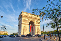 Arc de Triomphe. PARIS, FRANCE - MAY 10, 2017 : Arc de Triomphe with french flag in the evening. Triumphal Arch is one of the most famous monuments in Paris Stock Photos