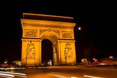 Arc de Triomphe. In Paris, France at night with traffic around it Stock Photos