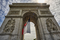 Arc de Triomphe. The Arc de Triomphe in Paris, France seen from the front. French flag hanging in the middle of the arch. Statues of heroes sculpted on both Stock Photo