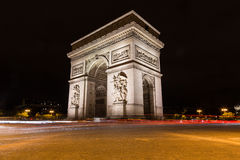Arc de Triomphe in Paris. PARIS, FRANCE - 28TH JULY 2016: The Arc de Triomphe in Paris at night. The blur of traffic can be seen Royalty Free Stock Image