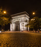 Arc de Triomphe in Paris. PARIS, FRANCE - 28TH JULY 2016: The Arc de Triomphe in Paris at night. People and the blur of traffic can be seen Royalty Free Stock Photography