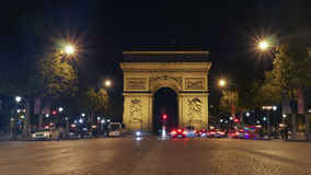 Arc de Triomphe, Paris illuminated at night. View along the Champs Elysees of the Arc de Triomphe, Paris illuminated at night with vehicular traffic on the Stock Photo