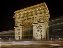 Arc de Triomphe in Paris at night. Arc de Trionphe and Light trails of Parisian traffic at night Stock Images