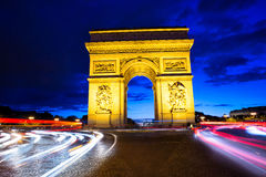 Arc de Triomphe, Paris, France at night. Blur of car headlights and taillights around illuminated Arc de Triomphe in Paris, France at night Royalty Free Stock Image