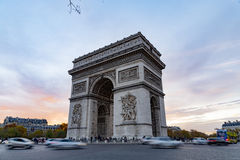 Arc de Triomphe in Paris. Traffic driving past the Arc de Triomphe at sunset in Paris, France Stock Image