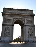 Arc De Triomphe. Shot taken in-between vehicles passing by this magnificent architecture. This is a morning shot with sun rising behind it Royalty Free Stock Image