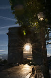 Arc de Triomphe with sunset in the middle Stock Images