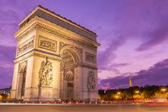 Arc de triomphe at sunset with violet sky. Amazing ornamental monument of Arc de Triomphe illuminated in twilight with violet sky on background Stock Photography