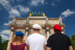 Arc de Triomphe and three people with berets in the colors of th Royalty Free Stock Photo