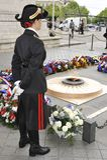 Arc de Triomphe, Tomb of the Unknown Soldier. Lady guard at the tomb of the unknown soldier and its eternal flame under the Arc de Triomphe, Paris Stock Photography