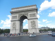 Arc de Triomphe with tourists around. Arc de Triomphe in Paris, France. Shot on a sunny day with many tourists around the area Royalty Free Stock Images