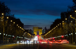 Arc de Triomphe and traffic. The Arc de Triomphe at the end of the Avenue des Champs-Elysees with the lights from traffic Royalty Free Stock Images