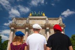 Arc de Triomphe y tres personas con las boinas en los colores del th Foto de archivo libre de regalías