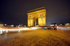 Arc de Triumph. Night time image of the famous Arc de Triumph with streams of car lights in Paris, France Royalty Free Stock Photos