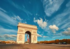 Arc de Triumph in Paris with beautiful clouds behind in Fall. Arc de Triumph in Paris with beautiful clouds behind on a bright afternoon in Autumn. Panoramic Stock Images