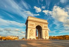 Arc de Triumph in Paris with beautiful clouds behind in Fall. Arc de Triumph in Paris with beautiful clouds behind on a bright afternoon in Autumn. Panoramic Stock Photo
