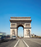 Arc de Triumph in Paris, France, on a bright sunny morning. Shot from the middle of the road, long exposure to blur passing traffic Stock Photos