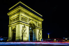 The Arc De Triumph. In Paris, France.  A night shot with the Eiffel tower nestled in the distance.  Light trails buzzing round this beautiful structure Royalty Free Stock Photo