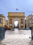 Arc de Triumphe in Montpellier. MONTPELLIER, FRANCE - MAR 31, 2017: Arc de Triumphe in Montpellier, dating from 1692, with surrounding buildings, people and Royalty Free Stock Photo