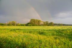 Arc-en-ciel après une pluie sur un champ rural Image libre de droits