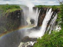 Arc-en-ciel au-dessus de Victoria Falls sur le fleuve de Zambezi Photographie stock libre de droits
