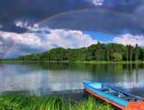 Arc-en-ciel au-dessus du lac avec un bateau Image stock