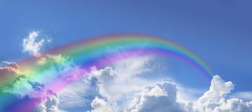 Arc-en-ciel courbant énorme sur le ciel bleu large Image stock