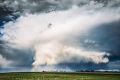 Arc-en-ciel dans le paysage rural de pré de ressort de champ de campagne sous le ciel dramatique scénique image libre de droits