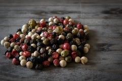Arc-en-ciel des grains de poivre sur une table en bois image stock