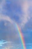 Arc-en-ciel en ciel nuageux bleu Images stock