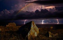Arc-en-ciel et ligtning au-dessus du bord de la mer Image libre de droits