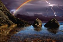 Arc-en-ciel et ligtning au-dessus du bord de la mer Photo libre de droits