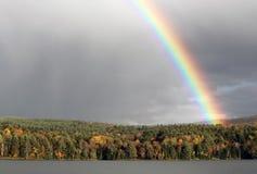 Arc-en-ciel lumineux et bel au-dessus des arbres et lac Photographie stock libre de droits