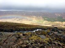 Arc-en-ciel menant dans le village au-dessous des falaises moussues en Islande Images libres de droits