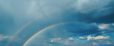 Arc-en-ciel primaire et secondaire à l'arrière-plan des nuages noirs Images libres de droits