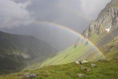 Arc-en-ciel s'étendant au-dessus d'une vallée de montagne devant l'orage foncé Image libre de droits