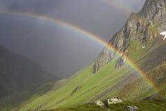 Arc-en-ciel s'étendant au-dessus d'une vallée de montagne devant la tempête foncée de tonnerre Photo stock