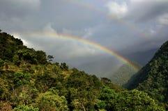 Arc-en-ciel sur le ciel nuageux, premier plan d'arbres, Sikkim Photographie stock libre de droits