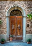 Arc entrance with old door to Tuscan house, Italy royalty free stock photography