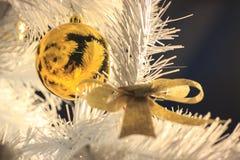 Arc et boule pour la décoration de couleur d'or avec des paillettes sur un arbre de Noël blanc Préparations de Noël, décoration à photo libre de droits