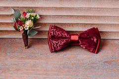 Arc et boutonniere rouges élégants sur le fond en bois, marié étant prêt dans le matin avant le mariage Photos libres de droits