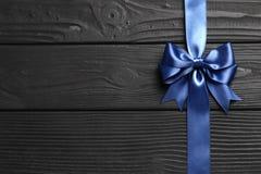 Arc et ruban bleus de cadeau sur un fond en bois noir photos stock