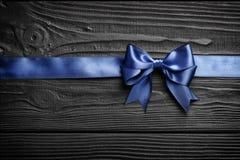 Arc et ruban bleus de cadeau sur un fond en bois noir photographie stock