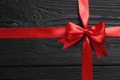 Arc et ruban rouges de cadeau sur un fond en bois noir image stock