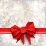 Arc et ruban rouges de papier de cadeau sur le fond argenté Photos libres de droits