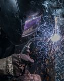 Arc flash light from a welding project. Man welding diamond plate with a mig welder Stock Photo