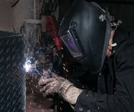 Arc flash light from a welding project. Man welding diamond plate with a mig welder Royalty Free Stock Images
