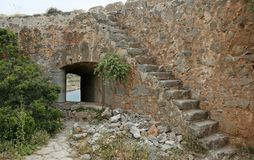 The arc in the old stone wall and the stone stairs. The arc in the old stone wall of the Venetian fortress and the stairs on the small Mediterranean island Royalty Free Stock Images