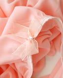 Arc rose sur la robe rose de tissu pour le fond Photo stock