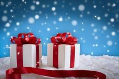 Arc rouge de cadeau sur la neige photo stock